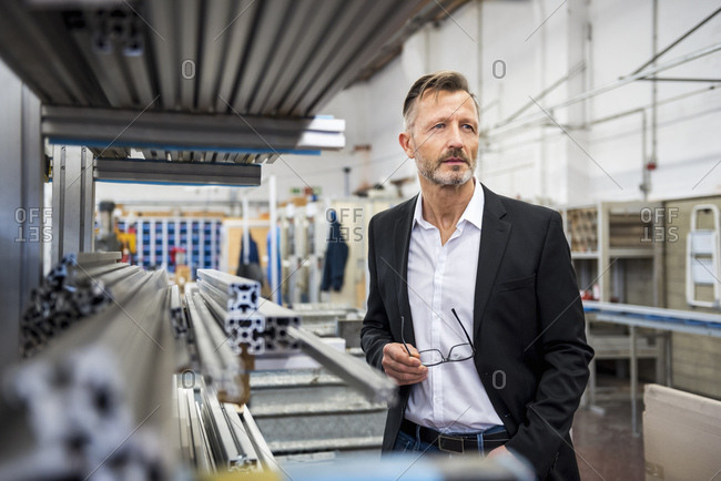 Mature businessman in factory thinking