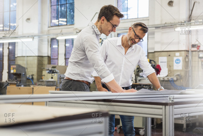 Two smiling businessmen in factory looking at plan