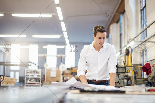 Young businessman in factory working on plan