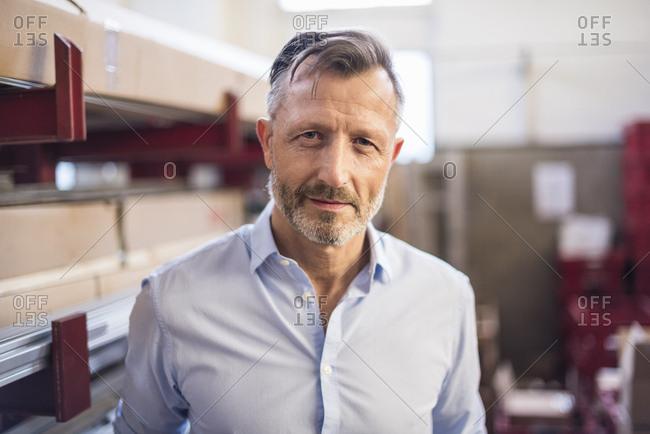 Portrait of confident mature businessman in factory storeroom