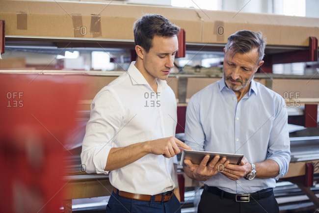 Two businessmen in factory storeroom looking at tablet