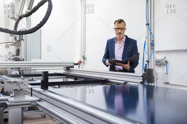 Mature businessman in solar factory holding folder