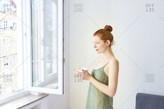 Portrait of pensive woman with bowl of white coffee standing near open window