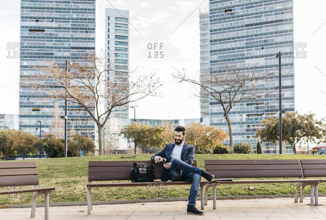 Businessman sitting on bench outside office building drinking coffee