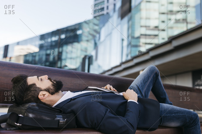 Businessman lying on bench outside office building