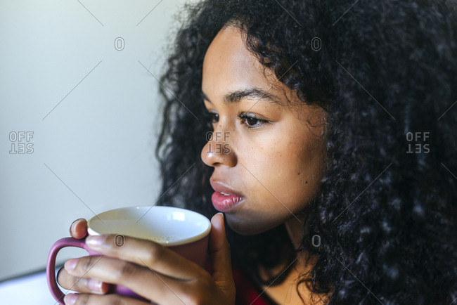Portrait of pensive young woman with cup of milk