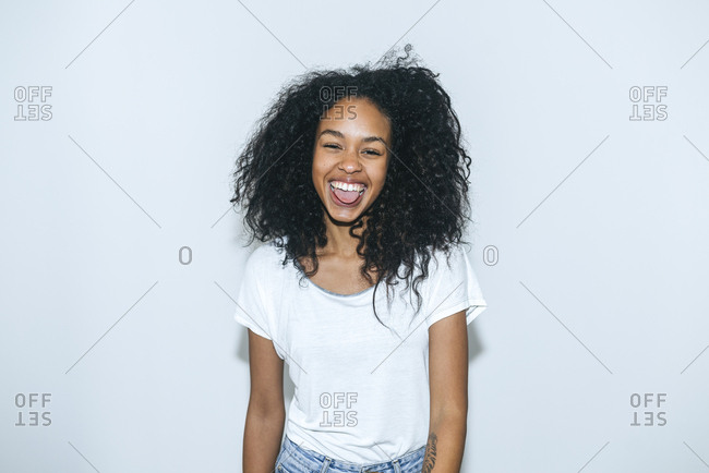 Portrait of laughing young woman sticking out tongue