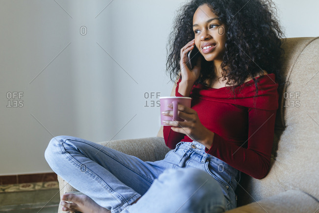 Portrait of smiling young woman on the phone sitting on armchair with a cup
