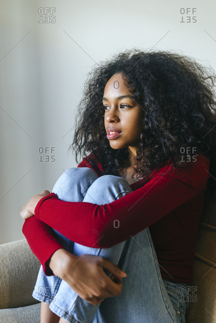 Portrait of pensive young woman sitting on armchair looking at distance