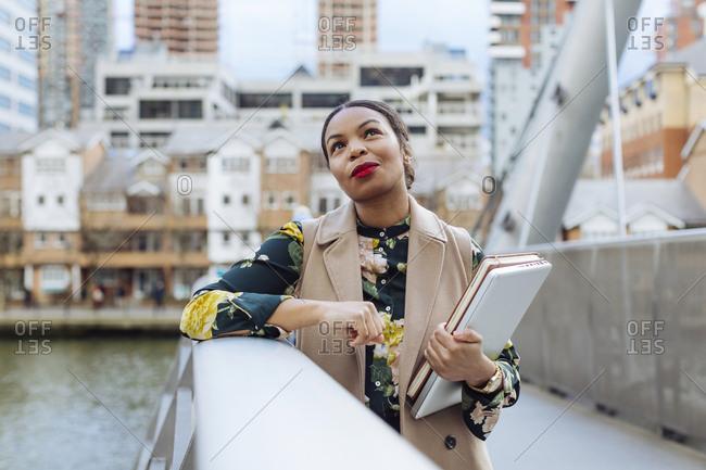 UK- London- portrait of fashionable  businesswoman leaning on railing of bridge
