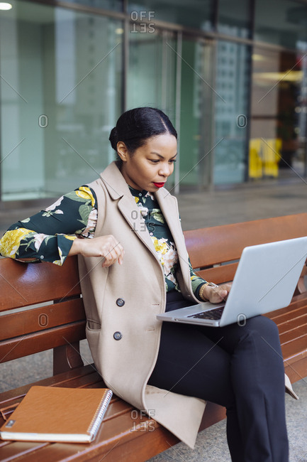 Businesswoman sitting on bench using laptop