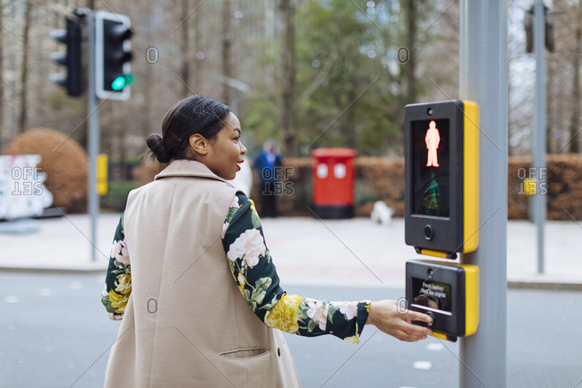 UK- London- woman pressing button of pedestrian light