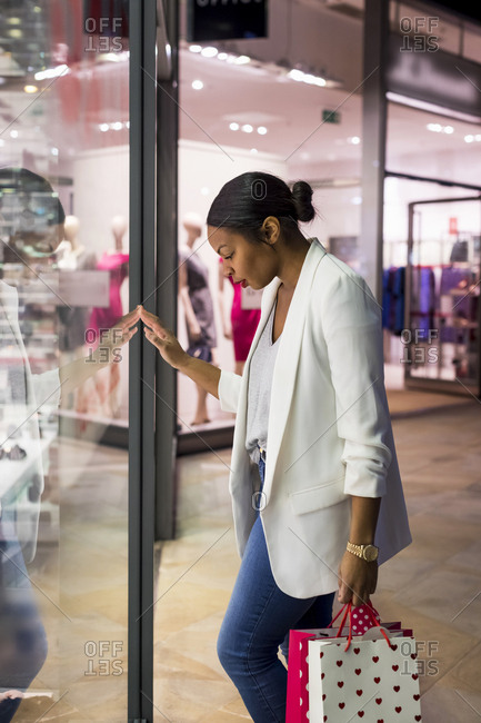 Woman looking in shop window of a fashion store