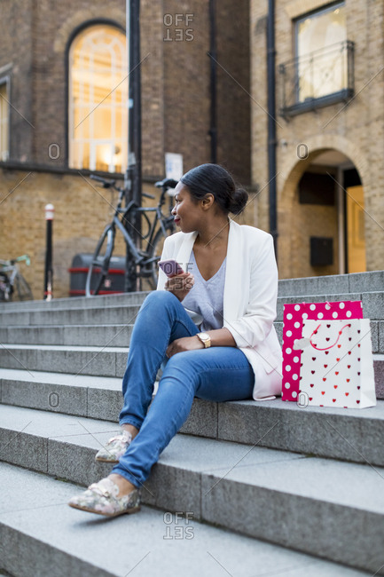 UK- London- woman with shopping bags and cell phone sitting on stairs in the city