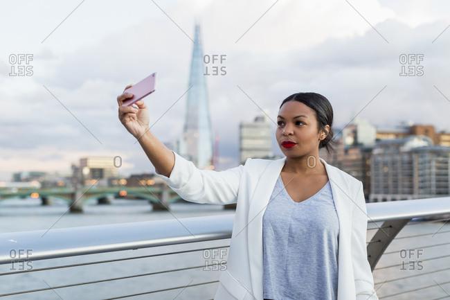 UK- London- woman standing on a bridge taking a selfie