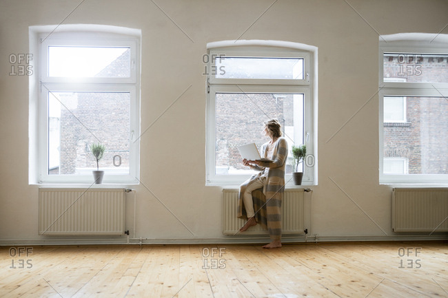 Mature woman in empty room holding laptop at the window