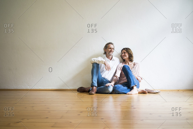 Smiling mature couple sitting on floor in empty room