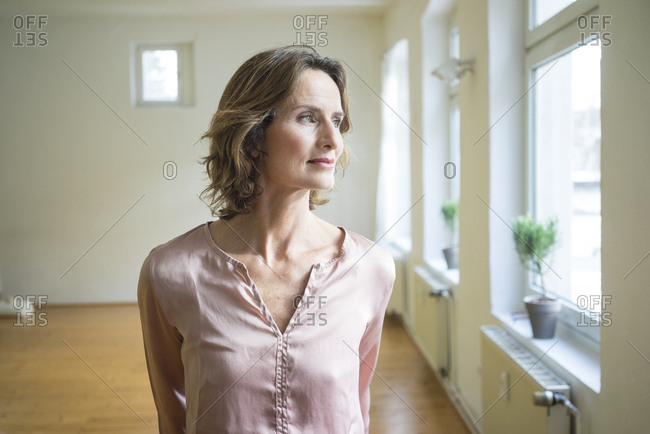 Pensive mature woman in empty room