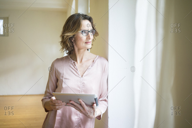 Mature woman in empty room holding tablet at the window