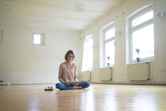 Mature woman sitting on floor in empty room using tablet