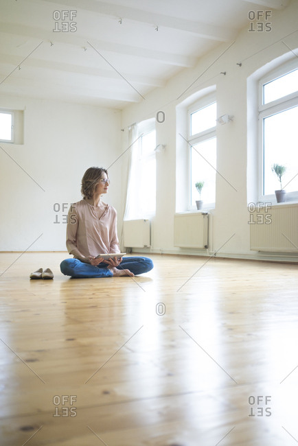 Mature woman sitting on floor in empty room with tablet