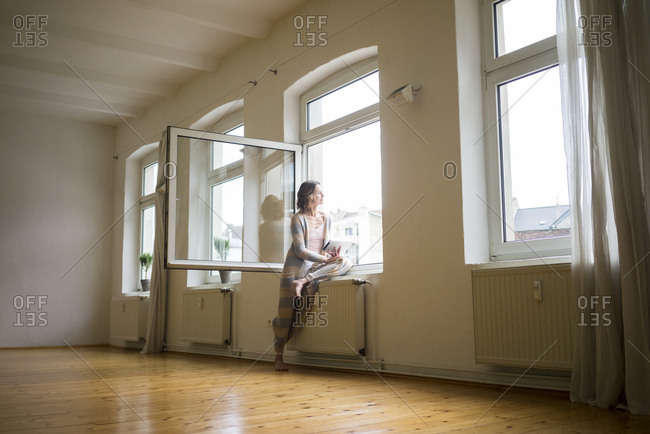 Mature woman in empty room holding tablet looking out of window
