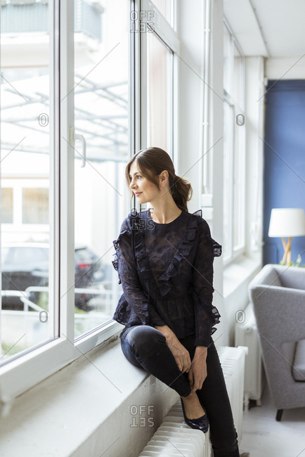 Woman sitting at the window looking out