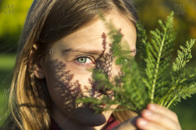 Portrait of girl with fern leaf at sunlight