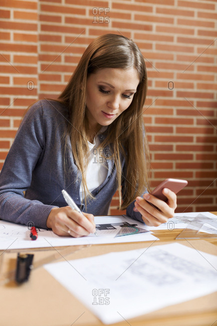 Young woman working in architecture office- using phone