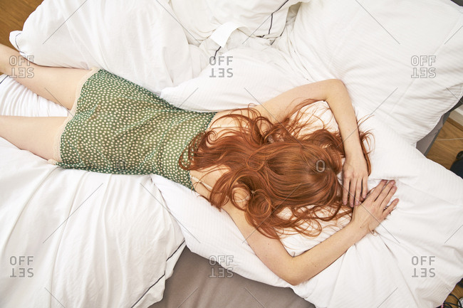 Back view of redheaded woman lying on bed
