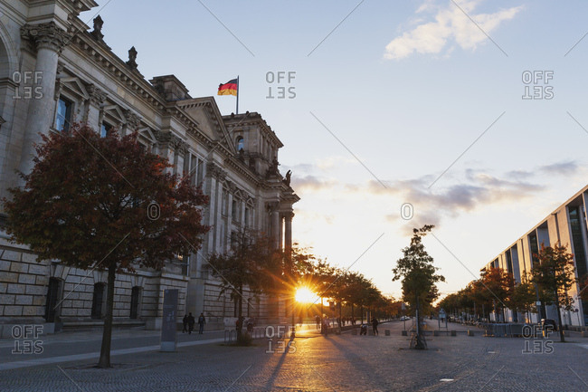 Germany- Berlin- Regierungsviertel- Reichstag building with German flags and Paul-Loebe-Building at sunset