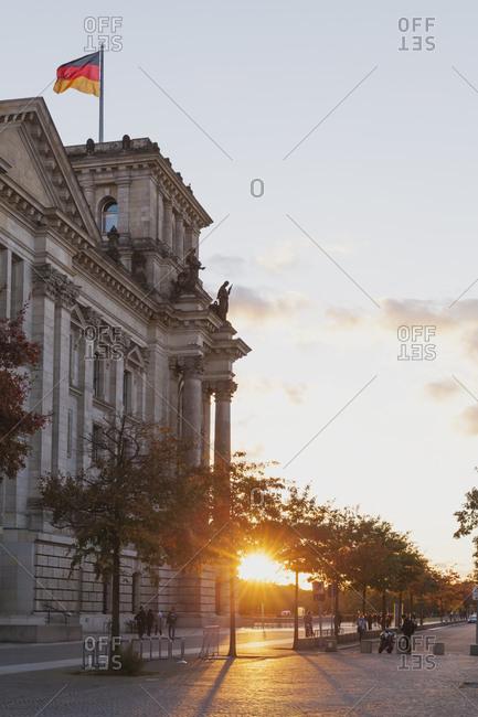 Germany- Berlin- Regierungsviertel- Reichstag building with German flag in autumn at sunset