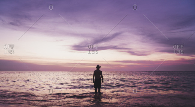 Thailand- Phuket- silhouette of man wearing hat wading at seafront by sunset