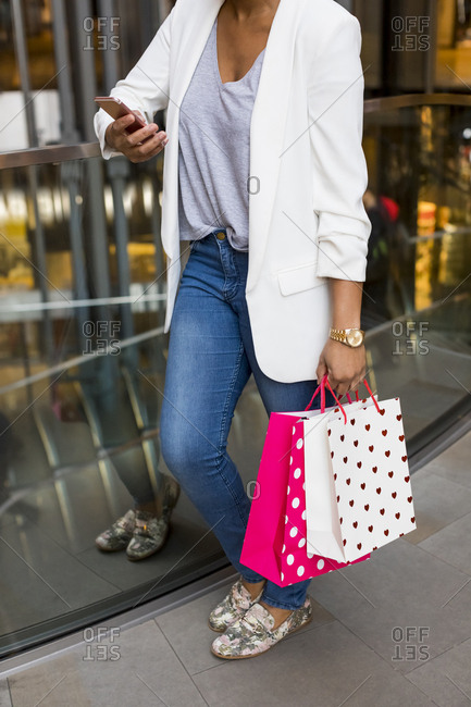 Woman using cell phone in shopping mall