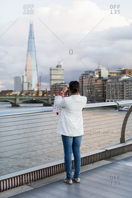 UK- London- woman standing on a bridge taking picture of The Shard