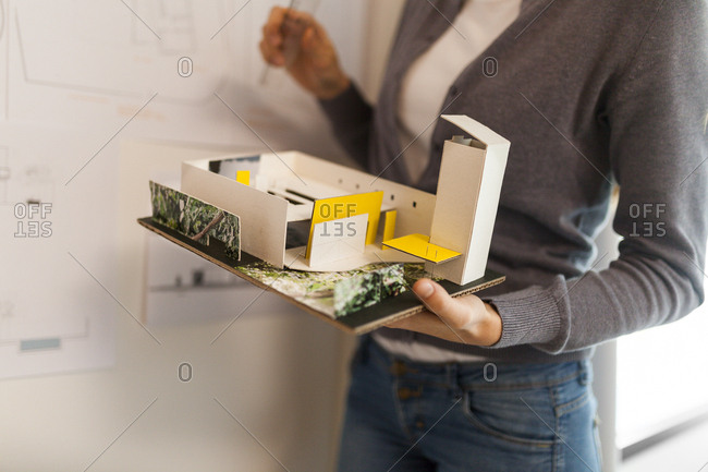 Female architect working on a project- holding architectural model