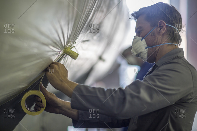Worker in a factory wearing dust mask taping