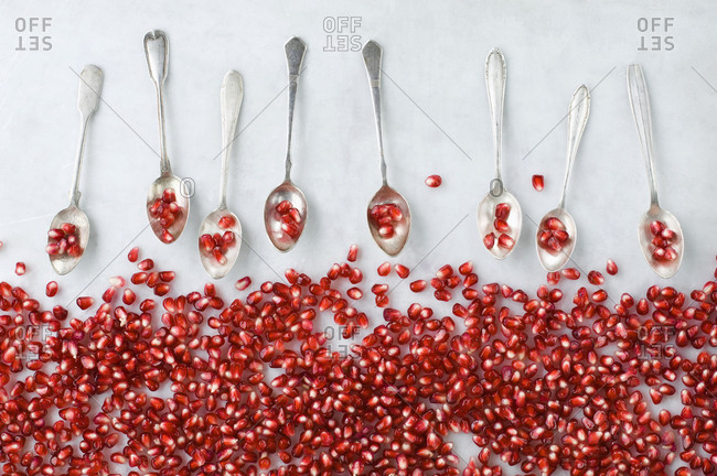 Pomegranate seeds and row of silver tea spoons on white marble