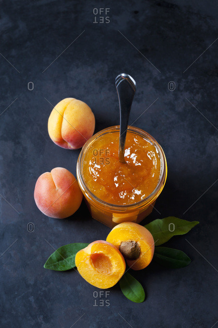 Glass of apricots jam and apricots on dark background