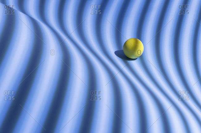 Yellow sphere over a geometric blue background- 3D Rendering
