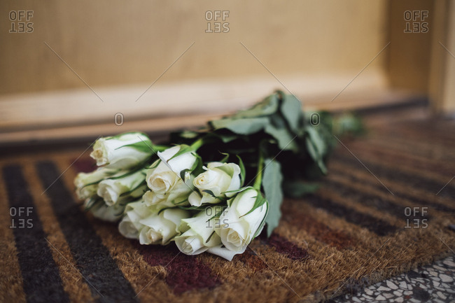 Bunch of white farewell flowers lying on floor mat at apartment door of deceased neighbor