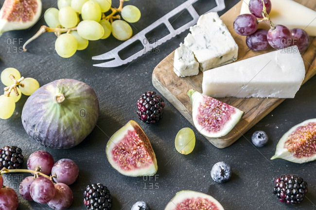 Plate with cheese- figs- grapes- blueberries- brambles- pecan- chopping board- knife