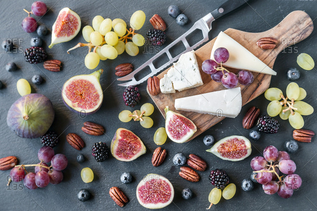 Plate with cheese- figs- grapes- blueberries- brambles- pecan nuts- chopping board- knife