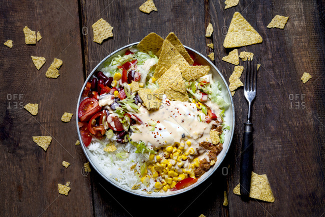 Taco salad bowl with rice- corn- chili con carne- kidney beans- iceberg lettuce- sour cream- nacho chips- tomatoes