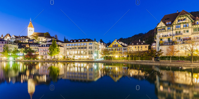Switzerland- Canton of Bern- Thun- river Aare- old town with parish church and Aarequai at blue hour