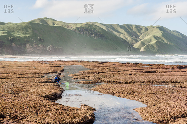 Boy exploring a sandy beach on the coast of New Zealand