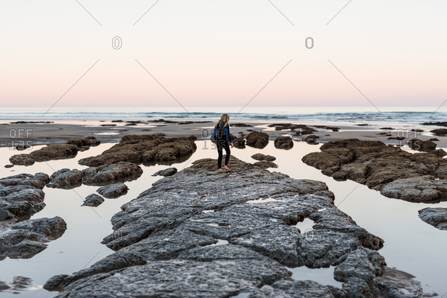 Rear view of girl exploring Hawke's Bay, New Zealand and it's tide pools