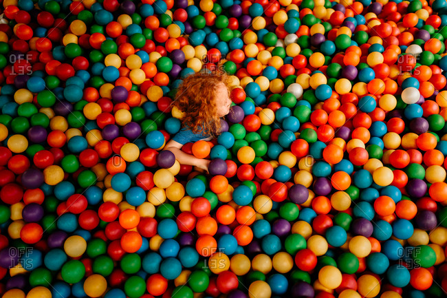 Boy neck high in in colorful ball pit