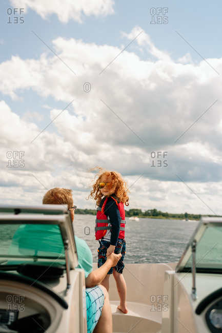 Father helping son prepare for jump on boat