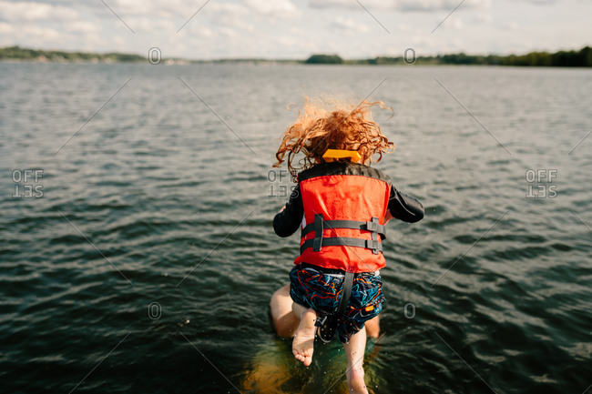 Child jumping to father from boat on the lake